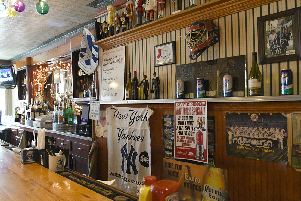 Long view of bar from one side, with sports memorabilia and nutcrackers on shelves