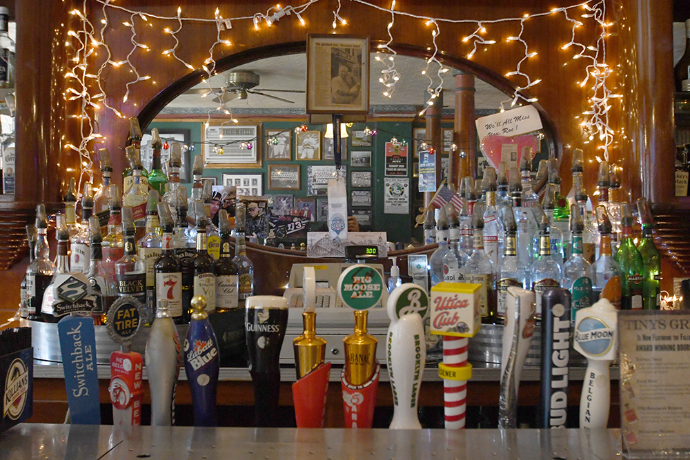 View of bar with beer taps in foreground, and large oval mirror strung with holiday lights