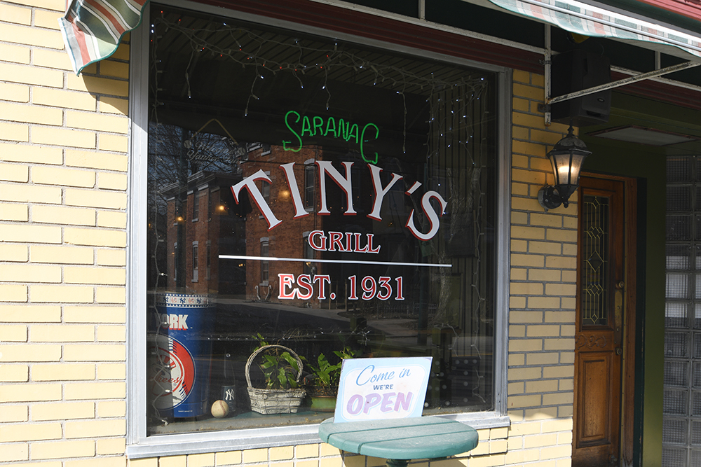 "Outside front window reading ""Tiny's Grill, Established 1931"" with Saranac neon sign"