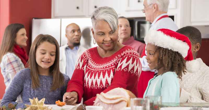 Multi-ethnic group of family members work together in a crowded kitchen to prepare dinner for a family Christmas celebration.