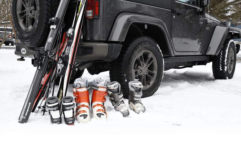 Skis, boots, and poles rest against a Jeep as family prepares for their financed ski vacation