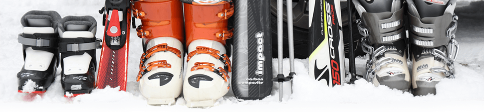 Skis, boots, and poles paid for with vacation financing sit in the snow near a car