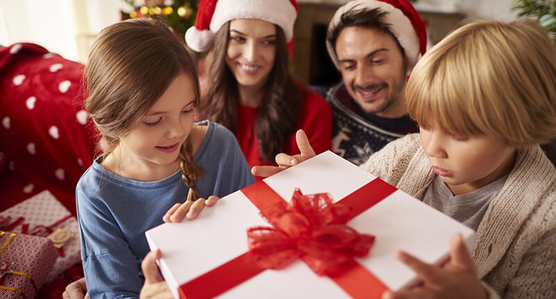 Children open a present as their parents watch, enjoying a holiday assisted by Holiday Loan financing