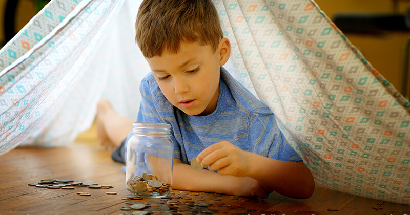 Young boy counting the coins he has saved.