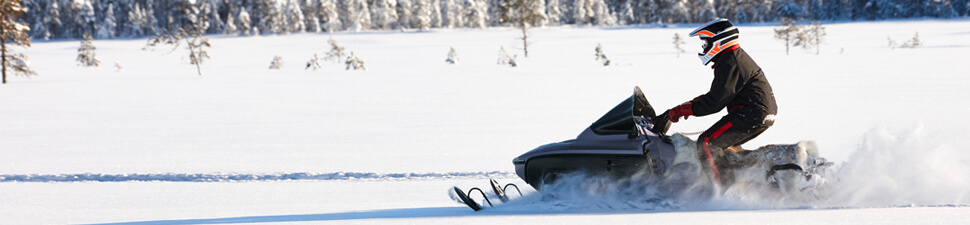 Snowmobile rider speeding across a snowy field, after receiving financing for his sled
